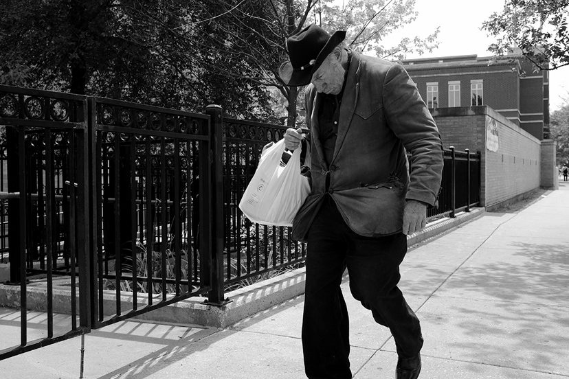 A man with a cowboy hat walking with his groceries.