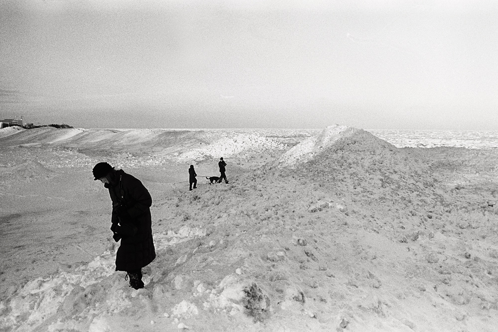 Several people walking across the frozen surface of Lake Michigan