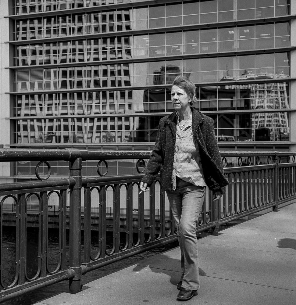 An older woman walks briskly across a bridge in downtown Chicago