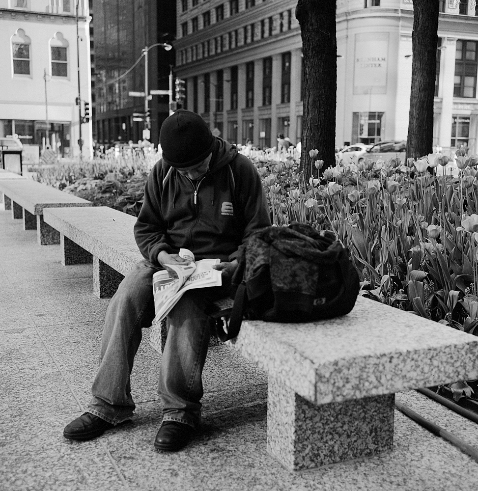 A man hunched over a newspaper