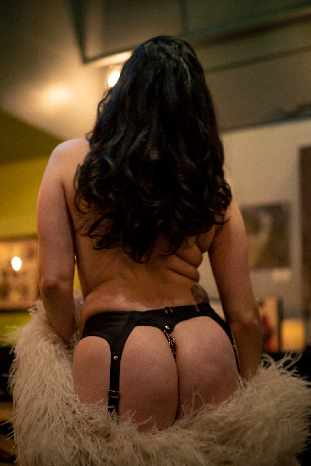 A semi-nude burlesque dancer photographed from behind