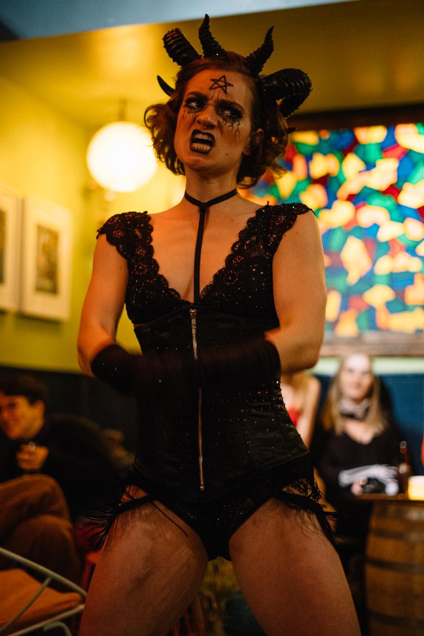 A burlesque dancer dressed in devilish lingerie
