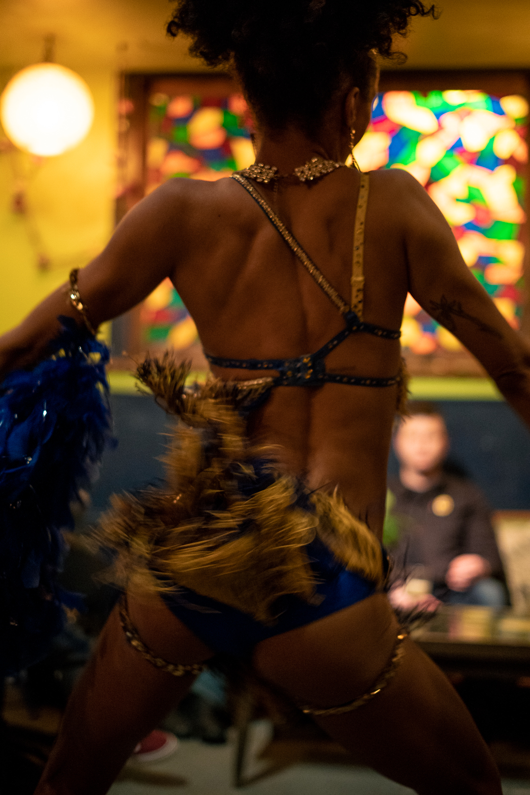 A photo from behind a burlesque dancer as they perform