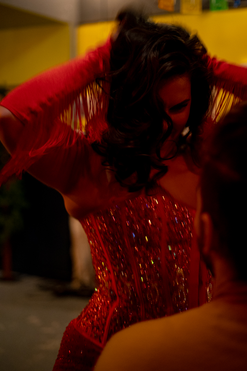 A mid-shot of a burlesque dancer in red