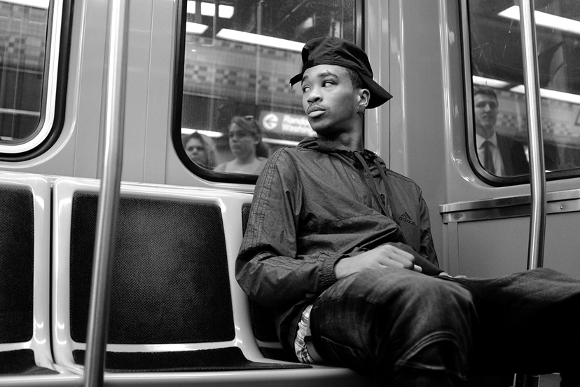 A young man peers through a train window