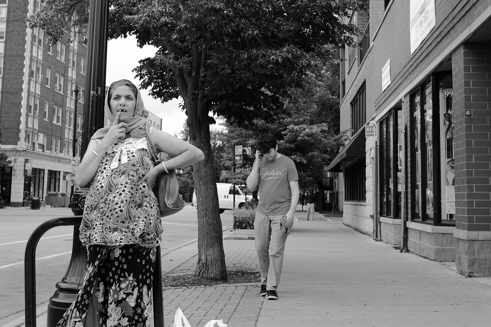 A street photograph of a woman pointing towards her missing tooth