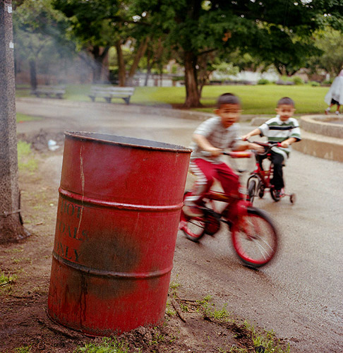 A fine art photo of a smoking red barrel in front of moving children. Part of my personal projects as a photographer in Lincoln NE.