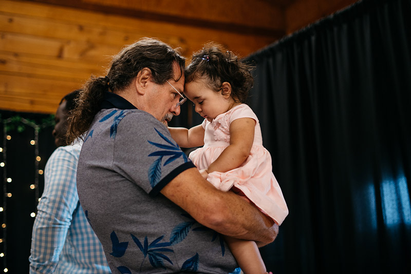 a sweet connection between grandfather and granddaughter during a reception