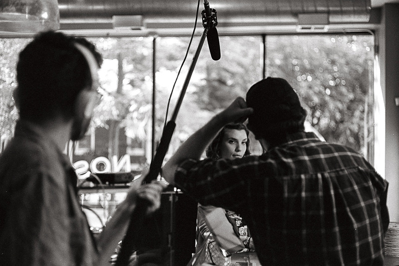 A behind the scenes portrait of an actress on a film set used as a thumbnail for photography services.