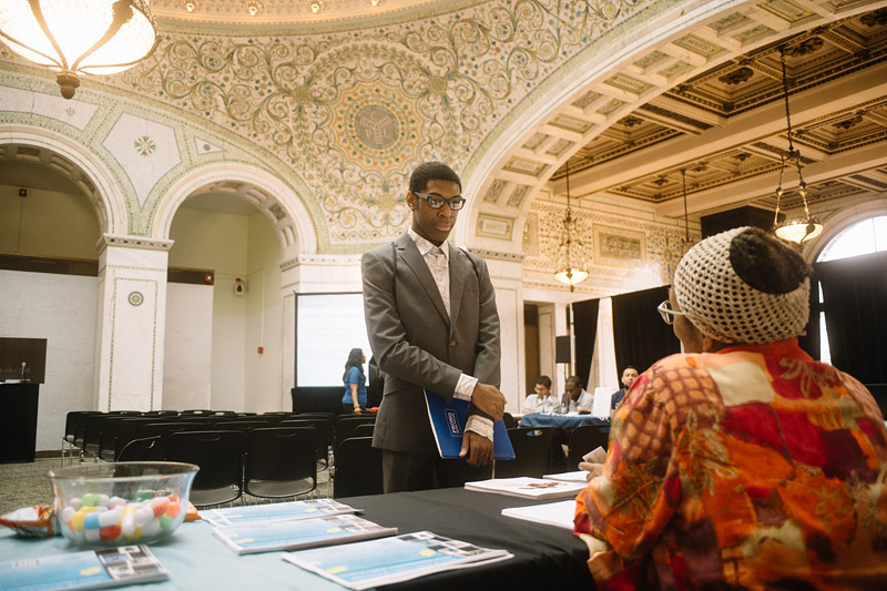 Photo of a young man speaking to an older woman at a job fair. Used for an events photographer thumbnail
