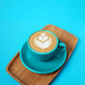 a cappuccino with latte art in a blue cup on a wooden plate against a blue backdrop